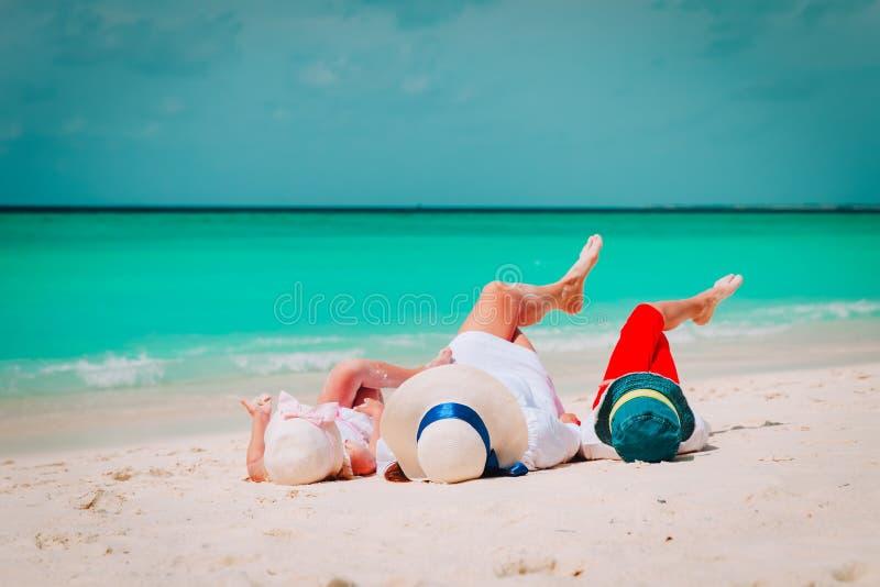 Den lyckliga mamman med sonen och dottern kopplar av på stranden arkivfoto