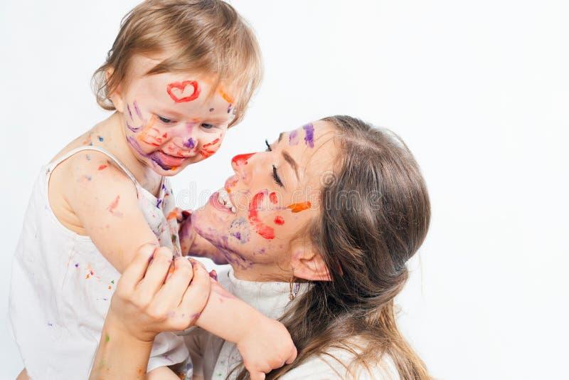 Den lyckliga mamman och behandla som ett barn att spela med den målade framsidan vid målarfärg royaltyfri bild