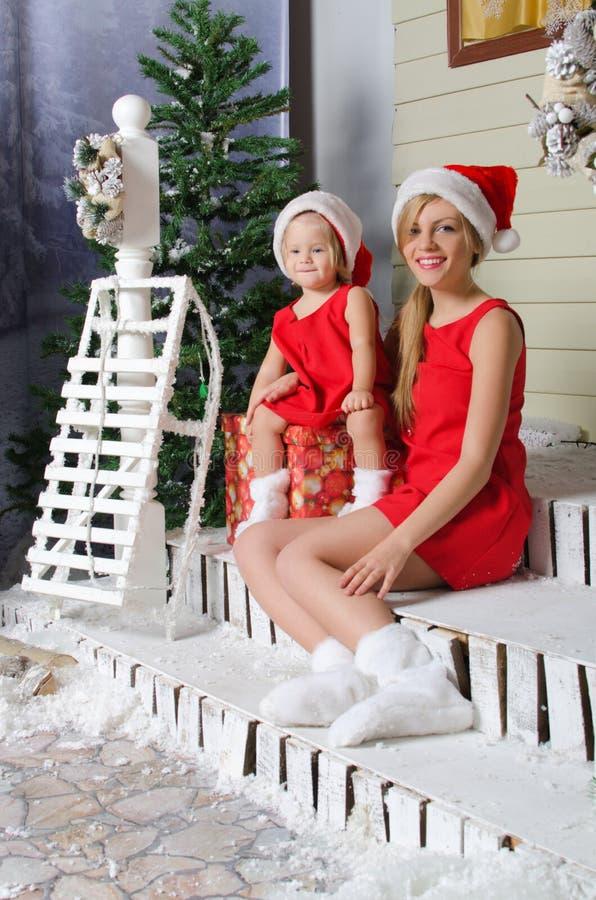Den lyckliga mamman och dottern i juldräkter sitter under snö arkivbilder