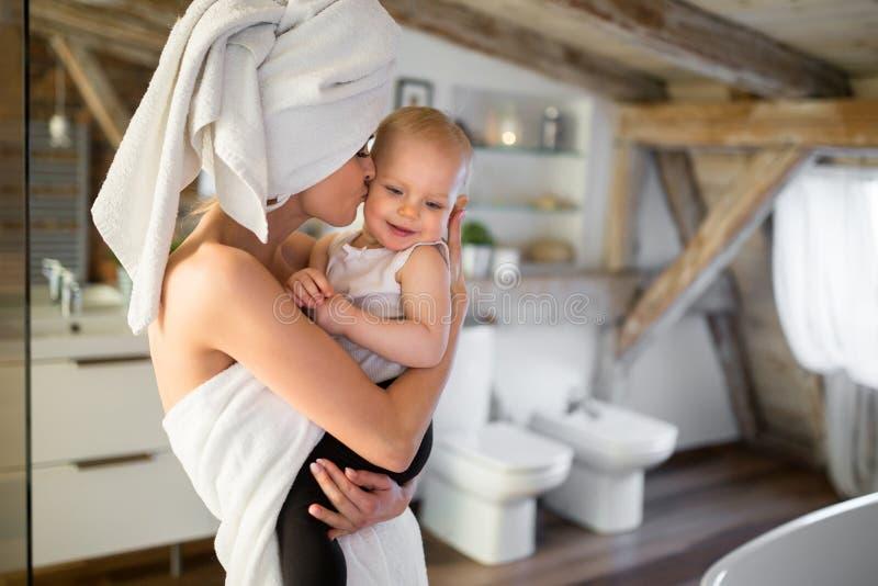 Den lyckliga mamman som kysser henne, behandla som ett barn i kind fotografering för bildbyråer