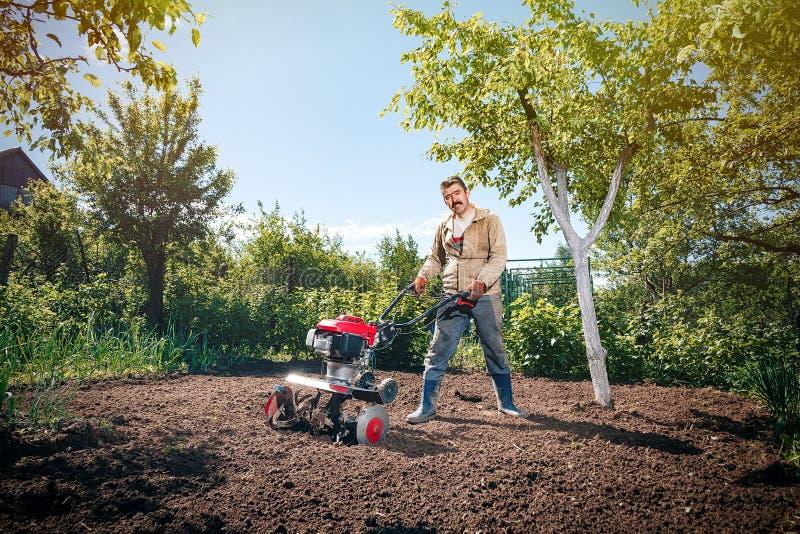 Den lyckliga manbonden plogar landet med en odlare som förbereder det arkivfoto