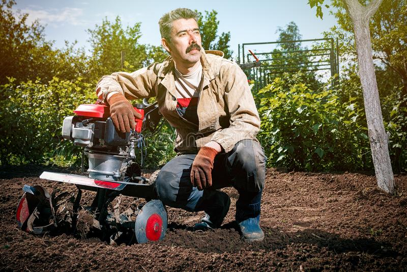 Den lyckliga manbonden plogar landet med en odlare som förbereder det royaltyfria foton