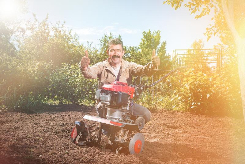 Den lyckliga manbonden plogar landet med en odlare som förbereder det royaltyfria bilder