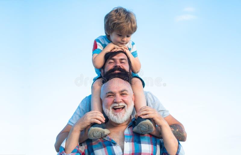 Den lyckliga manfamiljen har gyckel tillsammans Faderdag - farfadern, fadern och sonen kramar och har gyckel tillsammans royaltyfria foton