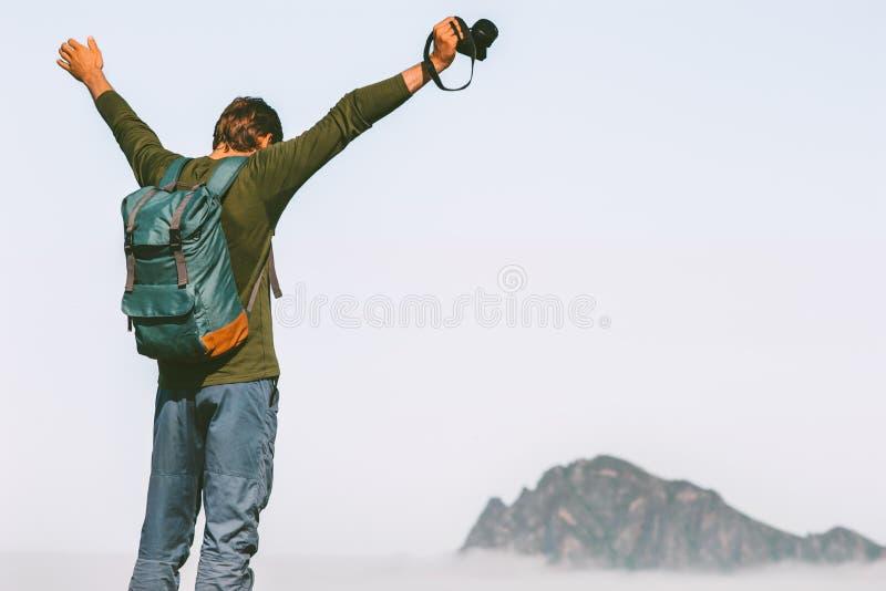 Den lyckliga manfotografen som reser i bergframgång, lyftte armar fotografering för bildbyråer