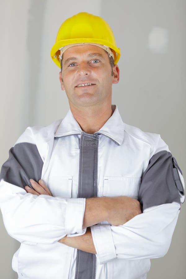Den lyckliga manliga byggm?staren i hj?lmanseende med armar korsade royaltyfri bild