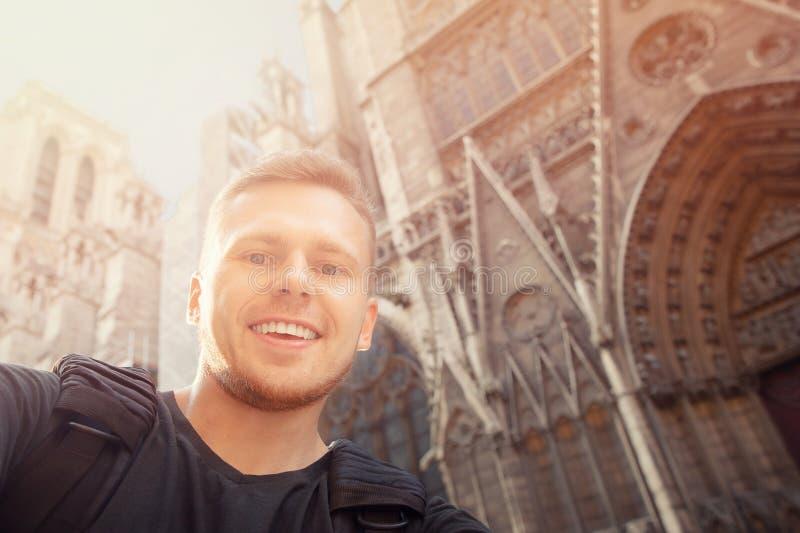 Den lyckliga manliga turisten tar selfiefotoet med Notre Dame de Paris France, ryggsäckskuldror Lopplivsstilbegrepp arkivfoto