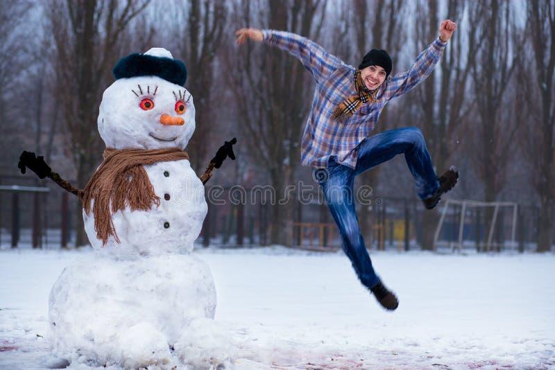 Den lyckliga mannen hugger den stora verkliga snögubben Den roliga mannen har gyckel i vinter parkerar royaltyfri bild
