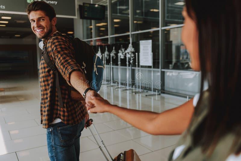 Den lyckliga mannen leder hans flickvän för att hyvla arkivfoto