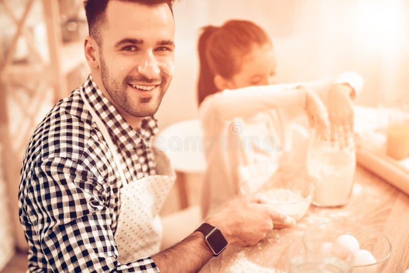 Den lyckliga mannen med flickan häller mjöl i Dihses på tabellen fotografering för bildbyråer