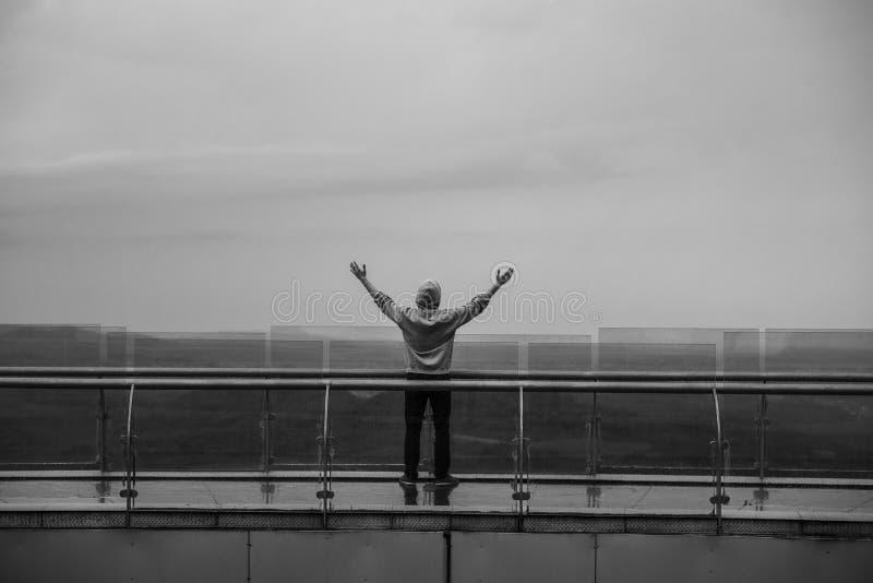 Den lyckliga mannen med händer up anseende i bergen royaltyfri foto