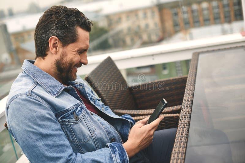 Den lyckliga mannen med skägget chating på telefonen royaltyfria bilder