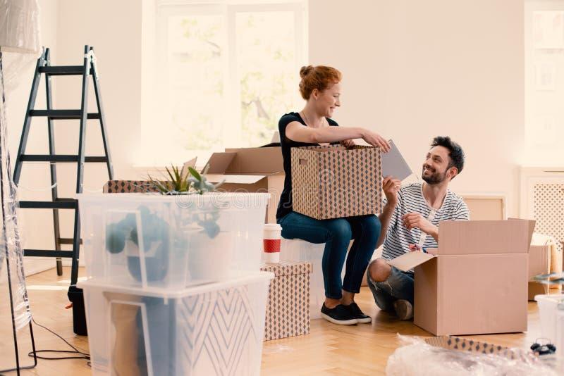 Den lyckliga mannen och kvinnan som packar upp material från tecknad film, boxas, medan möblera inre arkivfoton