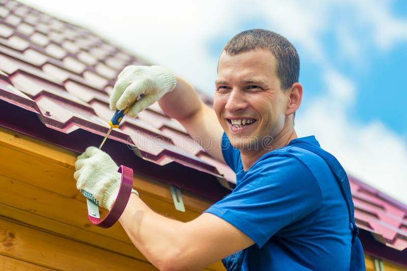 Den lyckliga mannen reparerar taket av huset, en stående på bakgrunden royaltyfria foton