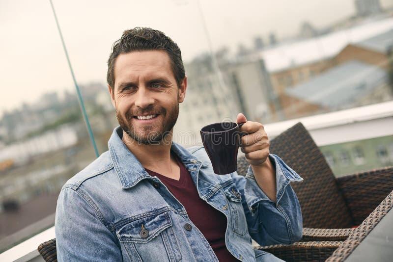 Den lyckliga mannen rymmer koppen i hand fotografering för bildbyråer