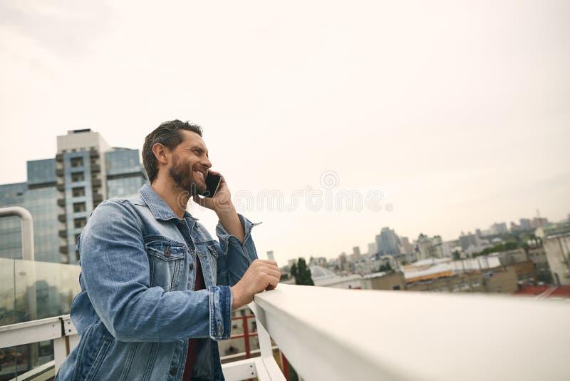 Den lyckliga mannen rymmer smartphonen i hand royaltyfria foton