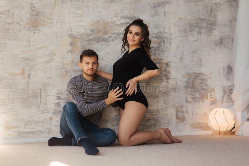 Den lyckliga mannen satte hans handr på buken av hans gravida fru Ung familj i studio Par väntar på för att behandla som ett barn royaltyfria bilder