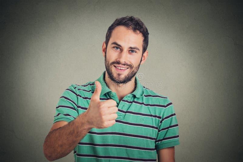 Den lyckliga mannen som ger tummar, up tecknet Positiv uttryckskroppsspråk för mänsklig framsida royaltyfri foto