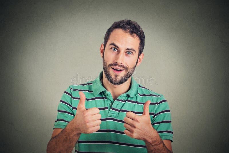 Den lyckliga mannen som ger tummar, up tecknet Positiv uttryckskroppsspråk för mänsklig framsida arkivbilder
