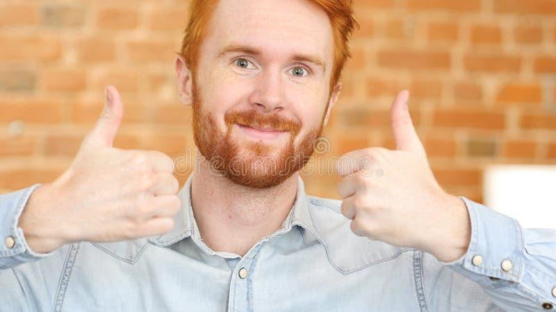 Den lyckliga mannen som ger tummar, up tecknet, stående arkivfoton