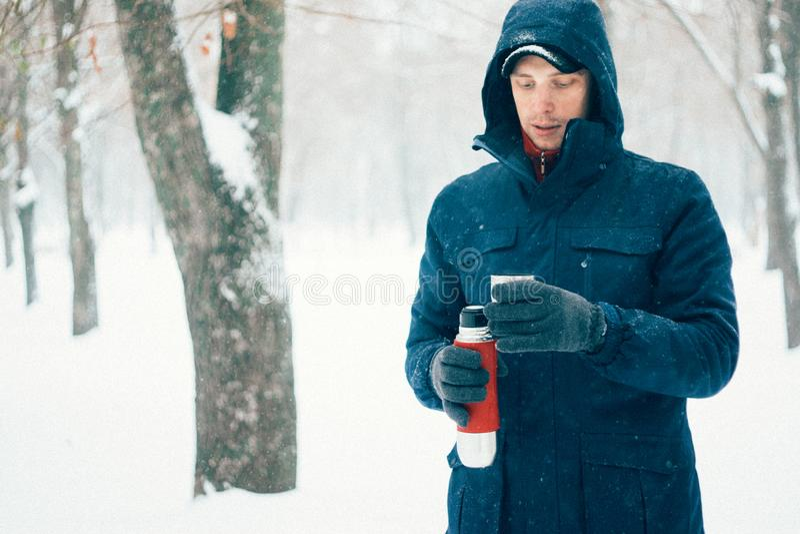Den lyckliga mannen som rymmer termoset parkerar in, med snö Ung man som dricker den varma drinken i skog i vintertid royaltyfria bilder