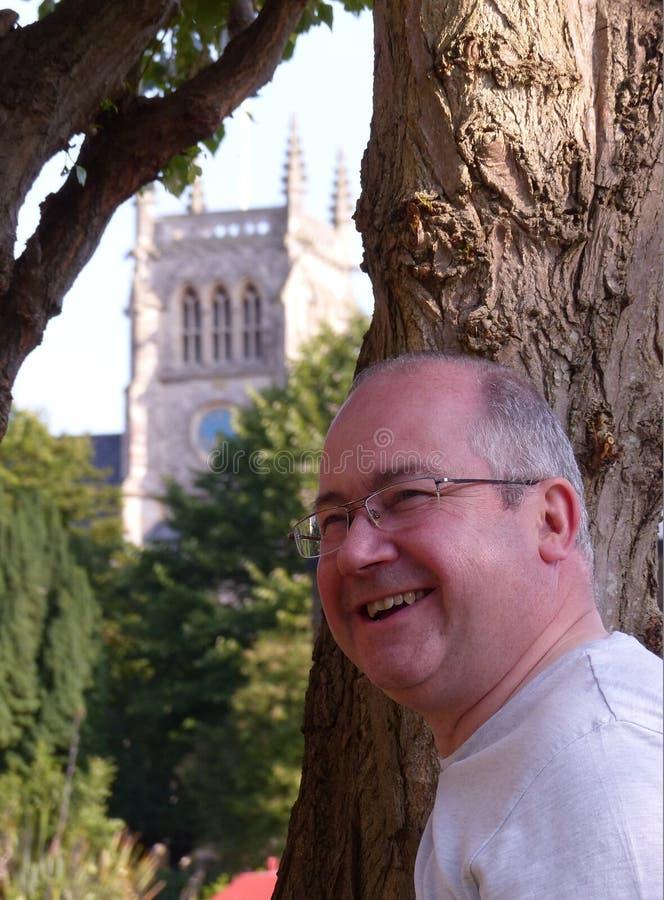 Den lyckliga mannen som stås av trädet nära, kyrktar royaltyfria bilder