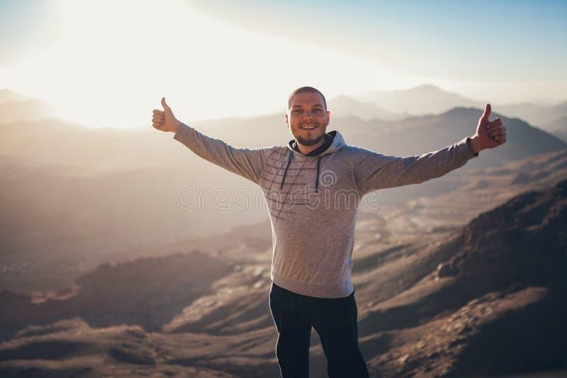 Den lyckliga mannen står mot bakgrund av soluppgång i Sinai berg royaltyfria foton