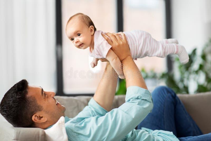 Den lyckliga mellersta åldriga fadern med behandla som ett barn hemma royaltyfri foto