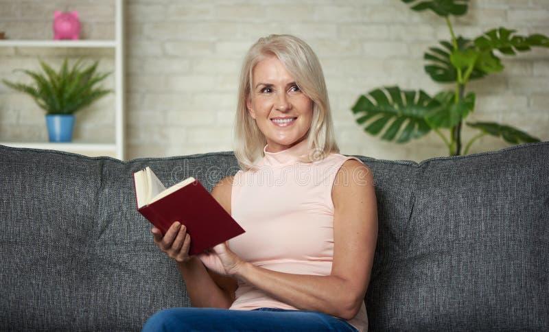 Den lyckliga mellersta åldriga kvinnan läser en bok arkivbilder