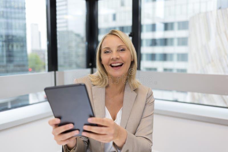 Den lyckliga mitt åldrades affärskvinnan som använder den digitala minnestavlan modernt kontor arkivfoto