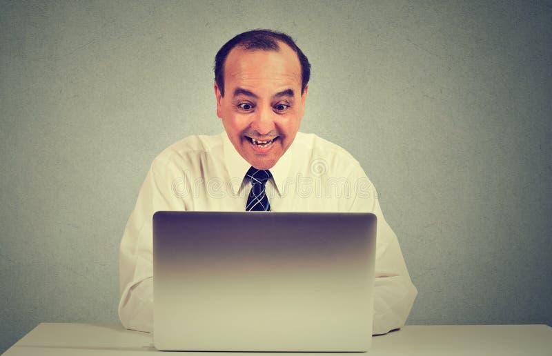 Den lyckliga mitt åldrades mannen som arbetar på en bärbar dator i hans kontor royaltyfri foto