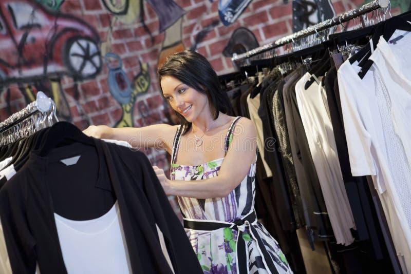 Den lyckliga mitt- vuxna kvinnan som bläddrar kläder, rack i modeboutique royaltyfria foton