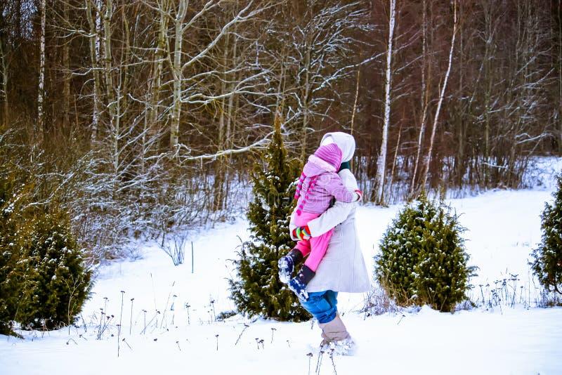 Den lyckliga moder- och barndottern som har gyckel som spelar på vintern, parkerar arkivbild