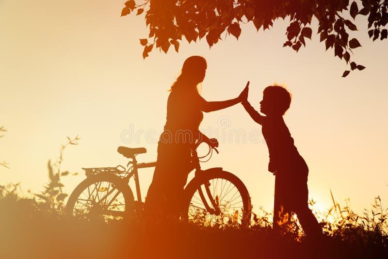 Den lyckliga moder- och sonridningen cyklar på solnedgången royaltyfri foto