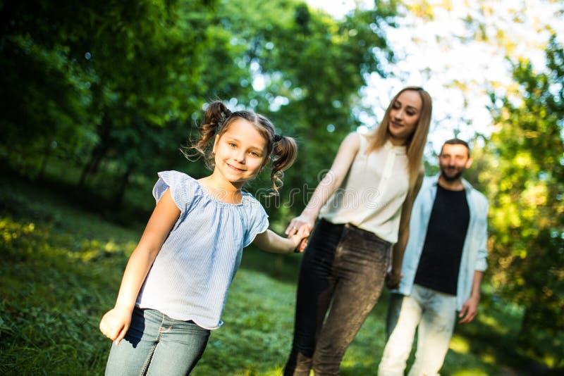 Den lyckliga modern, fadern och lilla flickan som går i sommar, parkerar och har gyckel royaltyfria foton
