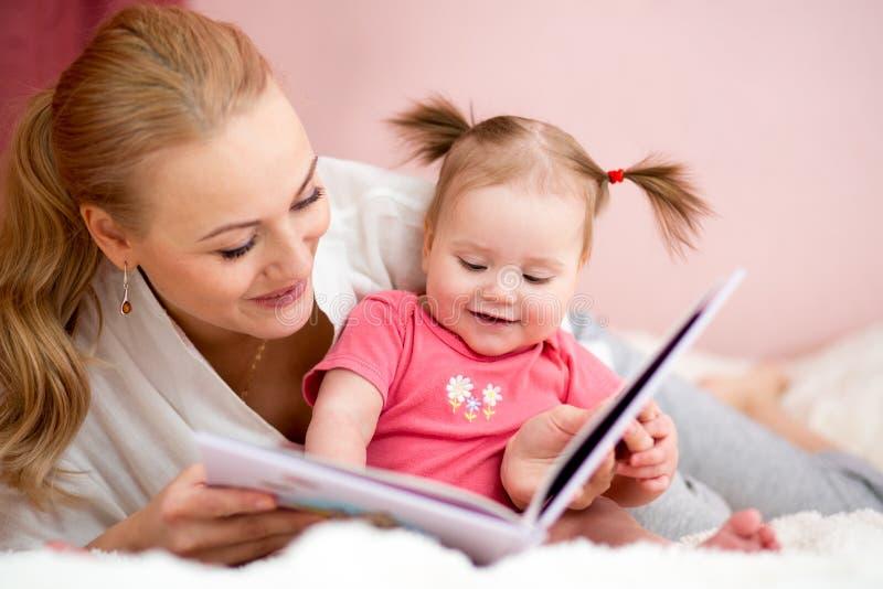 Den lyckliga modern läste en bok till behandla som ett barn flickan arkivfoton