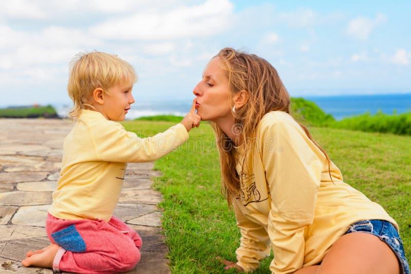 Den lyckliga modern med barnet har en gyckel på gräsgräsmatta royaltyfri foto