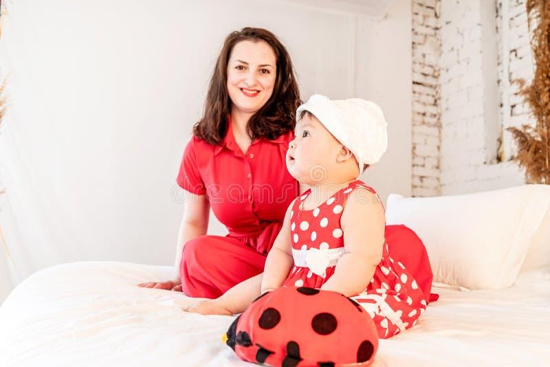 Den lyckliga modern med behandla som ett barn dottern som hemma spelar leksaker på vit säng arkivfoton