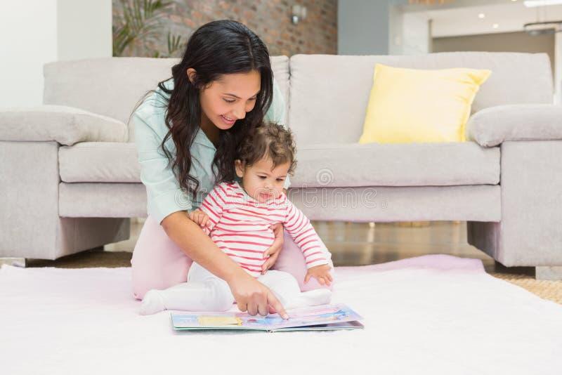 Den lyckliga modern med henne behandla som ett barn se en bok royaltyfria bilder