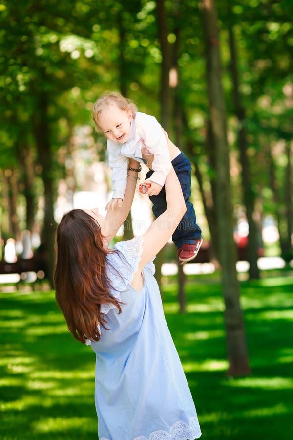 Den lyckliga modern med hennes behandla som ett barn pojken i parkera arkivbilder
