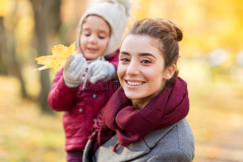 Den lyckliga modern med den lilla dottern på hösten parkerar fotografering för bildbyråer