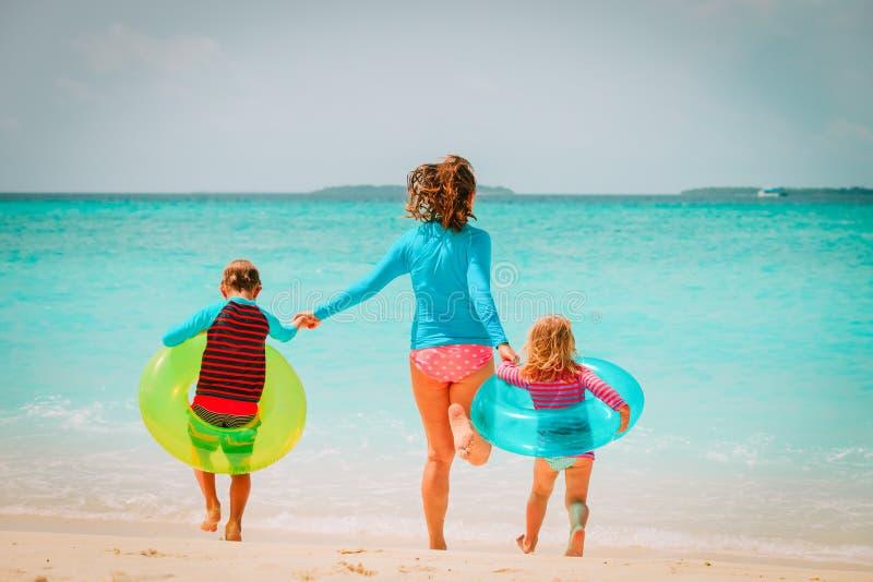 Den lyckliga modern med son- och dotterkörning har gyckel på stranden arkivfoto
