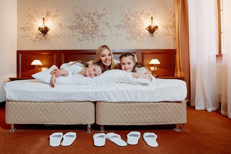 Den lyckliga modern och barn kopplar samman att krama i säng, i ett hemtrevligt hotell royaltyfria bilder