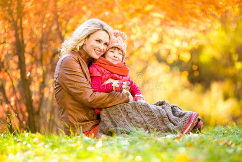 Den lyckliga modern och barnet som är utomhus- i höst, parkerar fotografering för bildbyråer