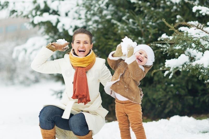 Den lyckliga modern och behandla som ett barn att kasta kastar snöboll i vinter parkerar arkivfoton