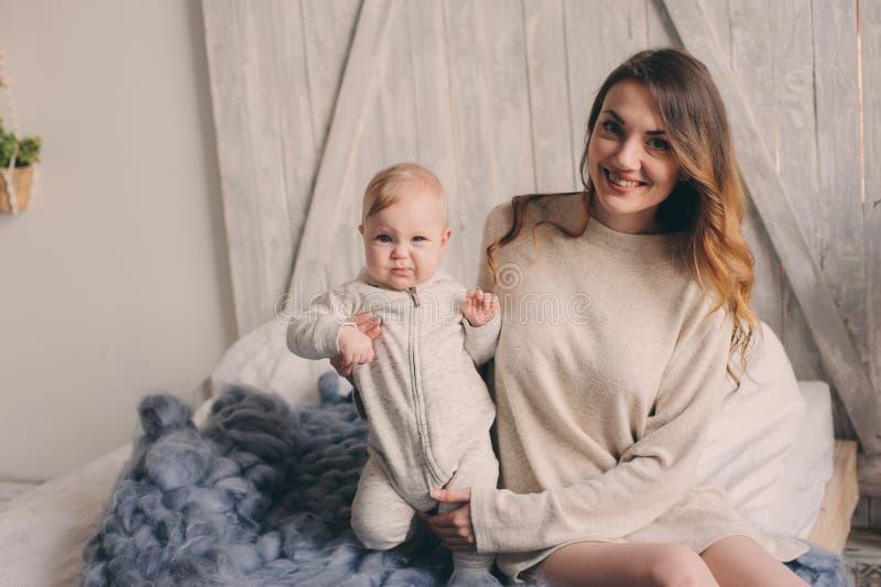 Den lyckliga modern och behandla som ett barn att spela hemma i sovrum Hemtrevlig familjlivsstil royaltyfria bilder