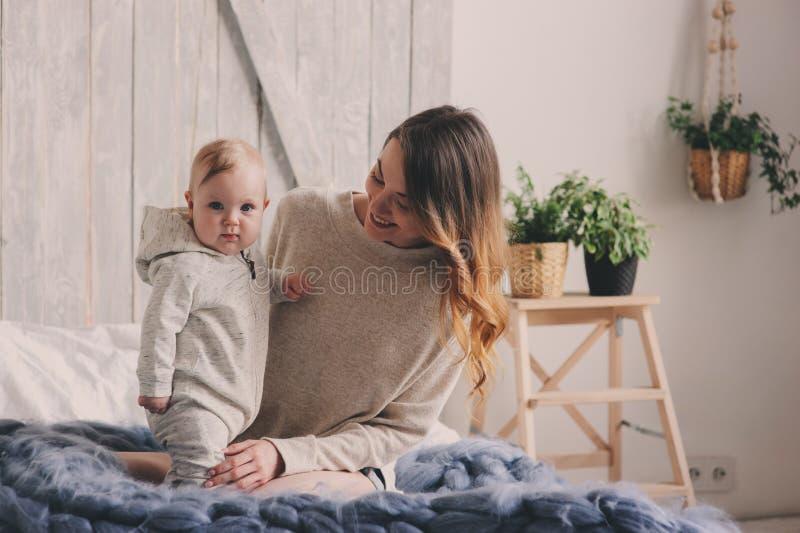 Den lyckliga modern och behandla som ett barn att spela hemma i sovrum Hemtrevlig familjlivsstil arkivbilder