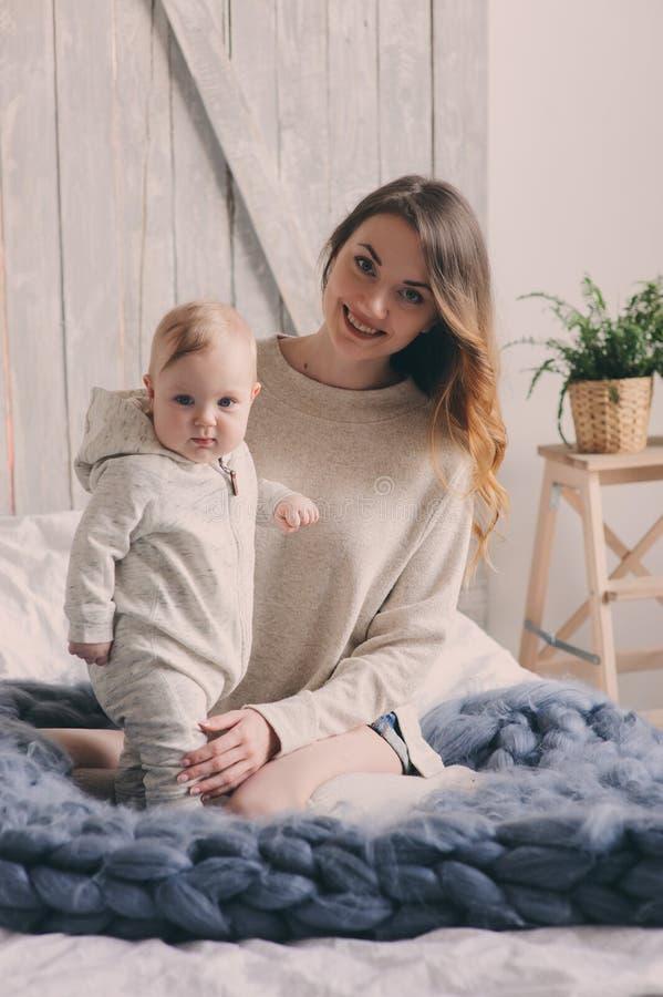 Den lyckliga modern och behandla som ett barn att spela hemma i sovrum Hemtrevlig familjlivsstil arkivfoton