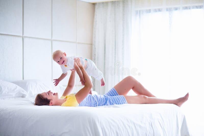 Den lyckliga modern och behandla som ett barn att spela i sovrum royaltyfri bild