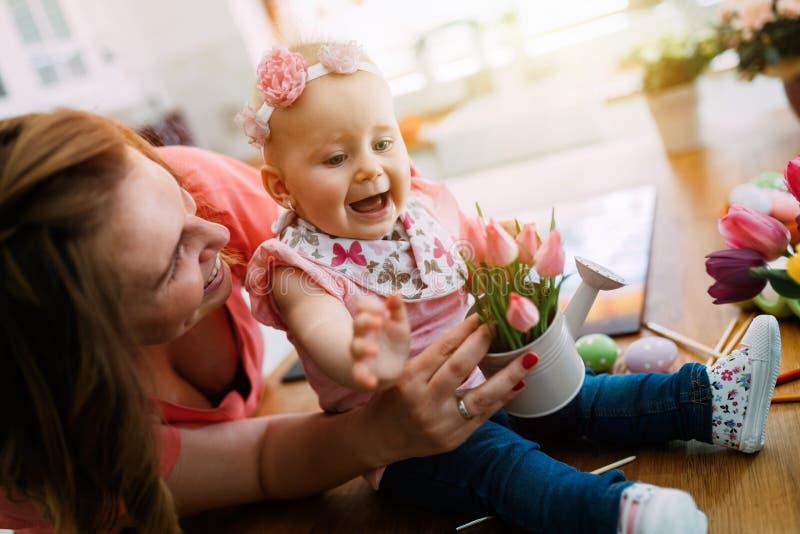 Den lyckliga modern och behandla som ett barn danandegarnering med buketten av tulpan fotografering för bildbyråer